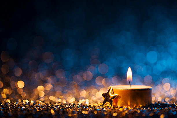 Lighted candle on defocused blue background - Christmas Tea Light stock photo