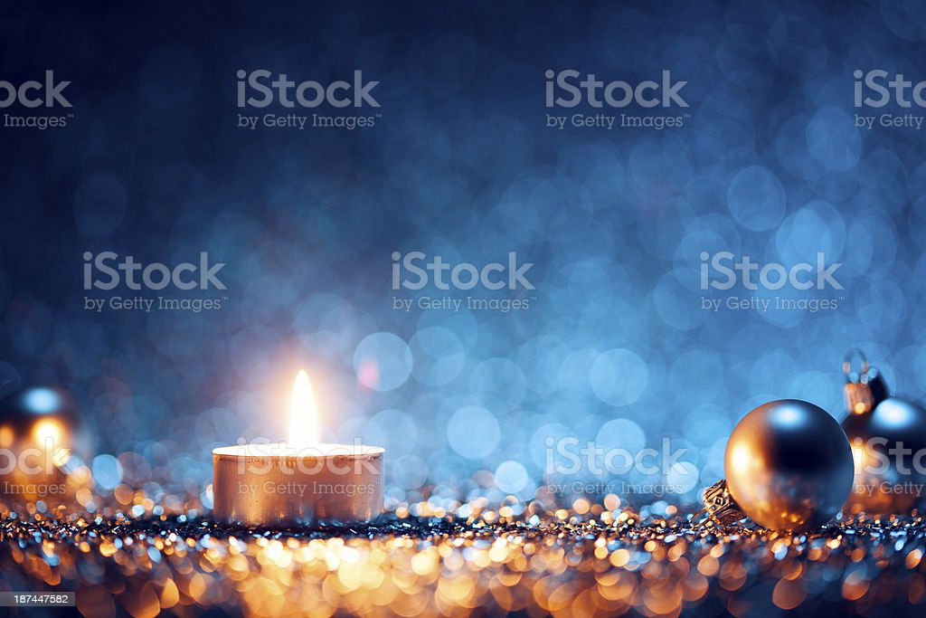 A lighted candle with Christmas balls at the sides royalty-free stock photo