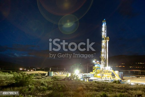 Well lit oil drilling Fracking Rig surrounded by green grass and bushes.  There are some clouds in the distance and lights on the Fracking Right side of the Fracking Rig.