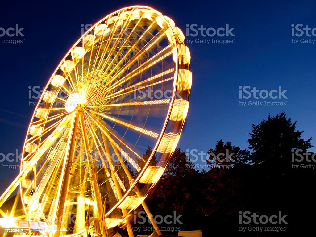 Lighted ferris wheel spinning in motion at night royalty-free stock photo