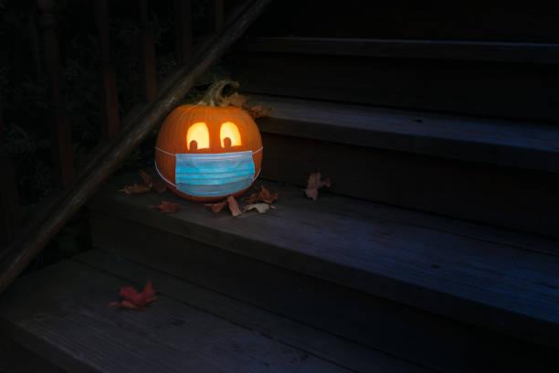 iluminado halloween jack o linterna calabaza usando máscara de epi covid en los pasos por la noche - halloween covid fotografías e imágenes de stock