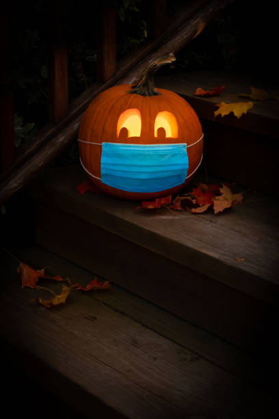 iluminado halloween jack o linterna calabaza usando máscara de epi covid - halloween covid fotografías e imágenes de stock