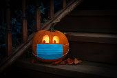 istock Lighted Halloween Pumpkin Jack o Lantern Wearing Covid PPE Mask On Steps 1272072577