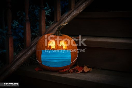 istock Lighted Halloween Pumpkin Jack o Lantern Wearing Covid PPE Mask On Steps 1272072577