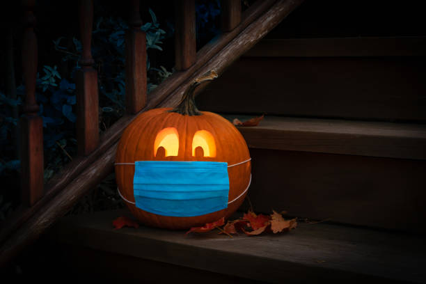 Lighted Halloween Pumpkin Jack o Lantern Wearing Covid PPE Mask On Steps Lighted Halloween Pumpkin Jack o Lantern Wearing Covid PPE Mask On Steps pumpkin stock pictures, royalty-free photos & images