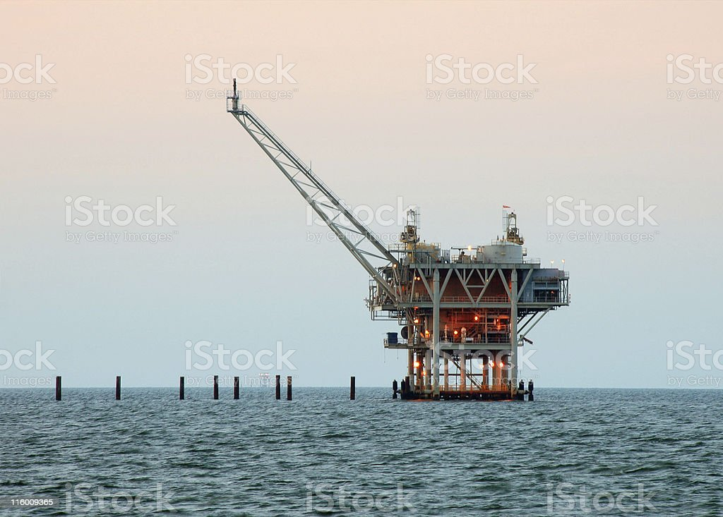 Lighted oil drilling rig in the middle of the ocean royalty-free stock photo