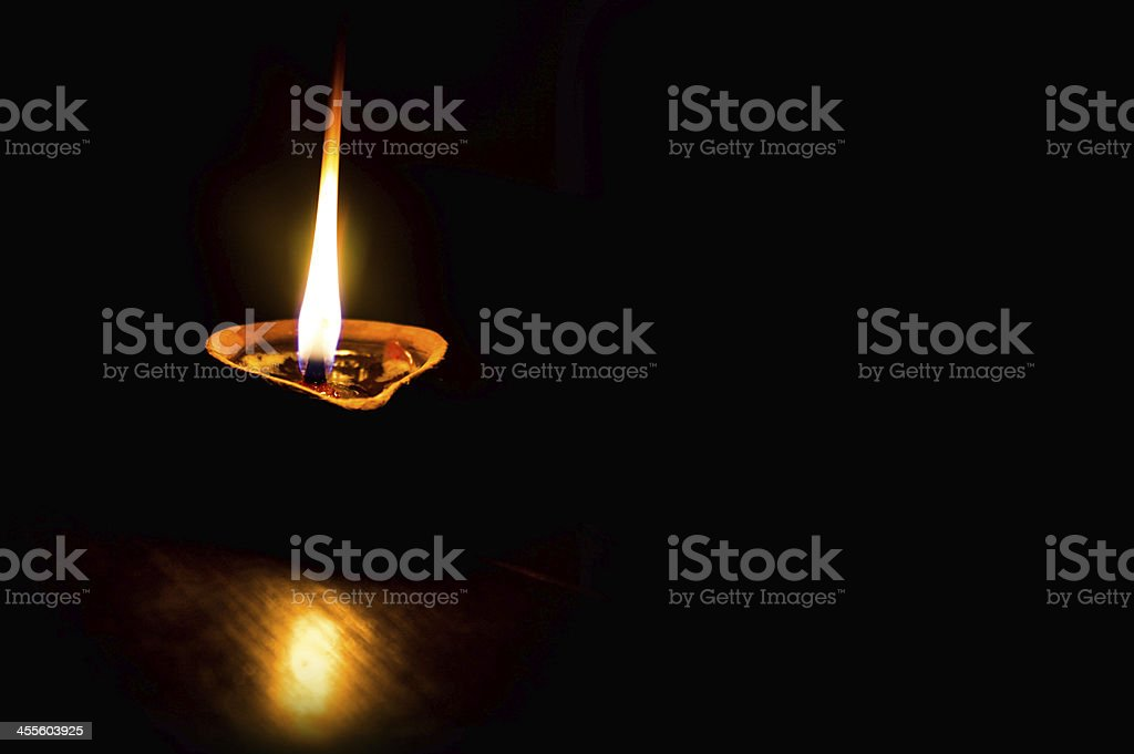 Lighted small clay lamp filled with oil in dark stock photo