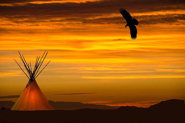 beleuchtete tipi und eagle overhead- orange sonnenuntergang - indianer tipi stock-fotos und bilder