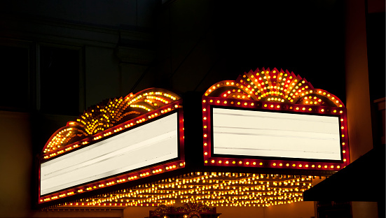 A bright theater marquee with glowing yellow light bulbs. There is a dark starry night sky in the background. The two marquee areas are blank so that you can easily add your own text. Large empty black areas in the sky are perfect for adding your headlines or body copy.