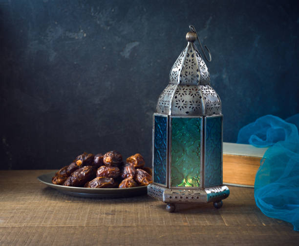 Lightened lantern and dates fruit on wooden table over dark background. Ramadan kareem holiday celebration concept stock photo
