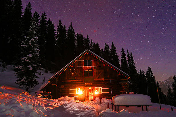 Lightened mountain hut in the austrian alps with milky way Lightened mountain hut in the Austrian alps with milky way. Scenic winter landscape. Night shot with 3200 ISO. chalet stock pictures, royalty-free photos & images