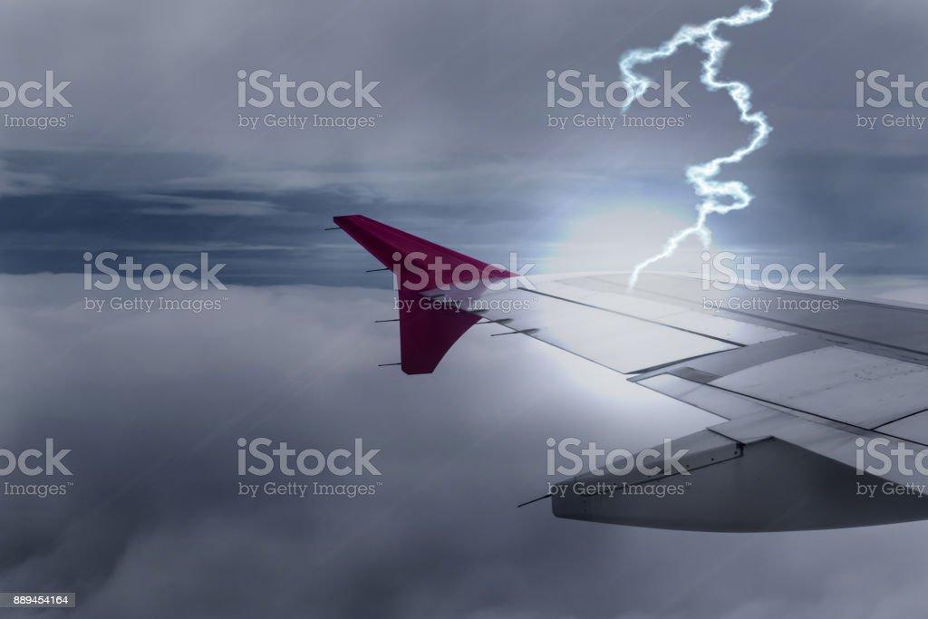 Relámpago golpea avión de ala de avión en el cielo oscuro - foto de stock