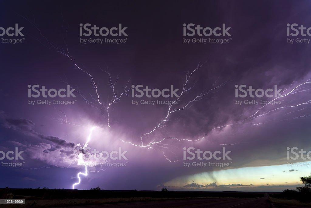 Lightening veining across stormy purple sky stock photo