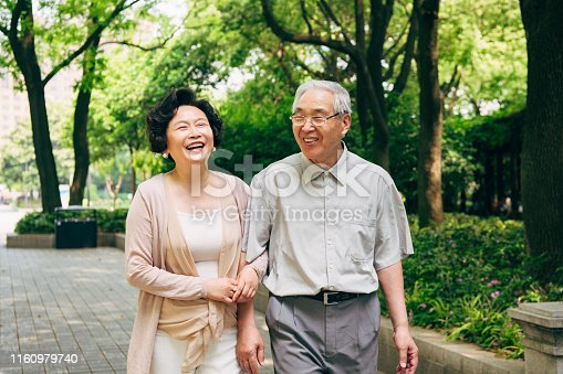 Cheerful senior Chinese couple spending a sunny spring day talking and walking through a Shanghai park.