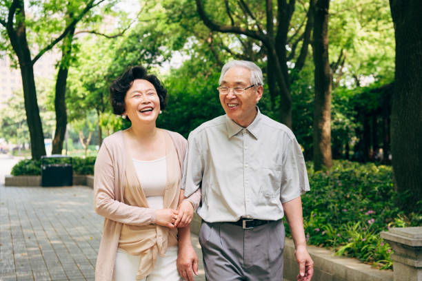 Lighthearted Chinese Seniors Walking at a Shanghai Park stock photo