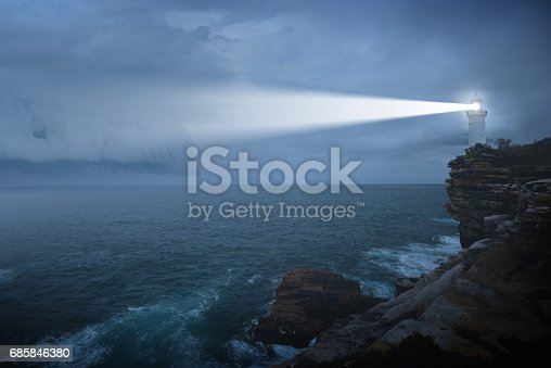 Lighthouse shines its light at against an angry-looking sky
