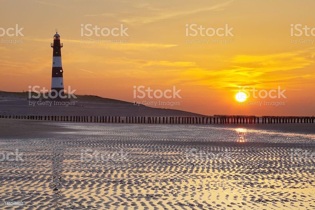 Lighthouse and beach at low tide at sunset, The Netherlands stock photo
