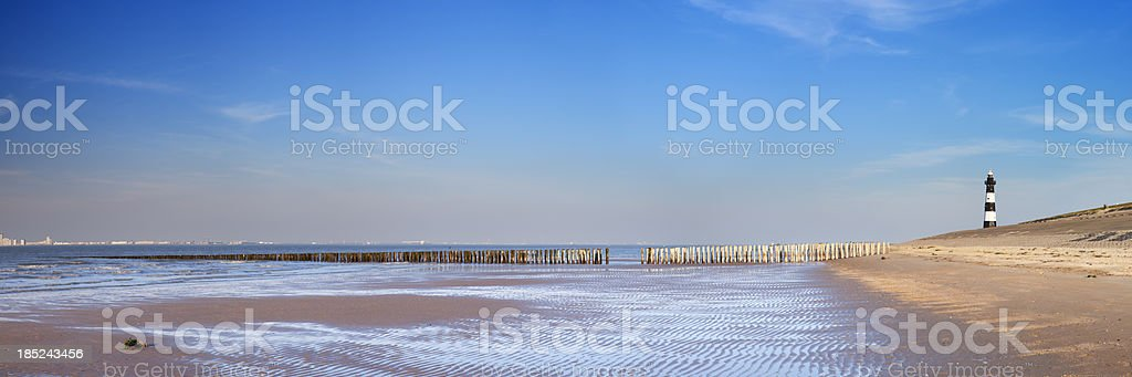 Lighthouse and beach at low tide in Zeeland, The Netherlands stock photo