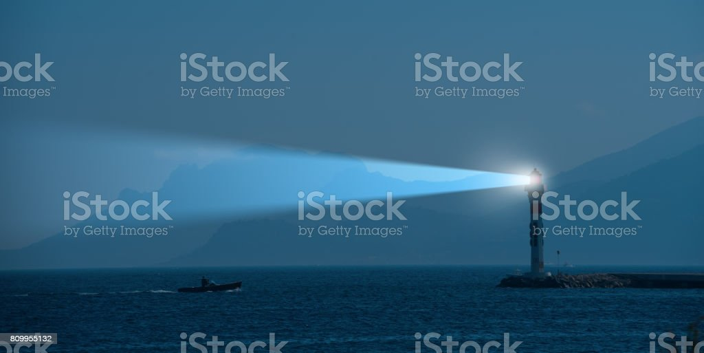 Lighthouse and beam at night stock photo