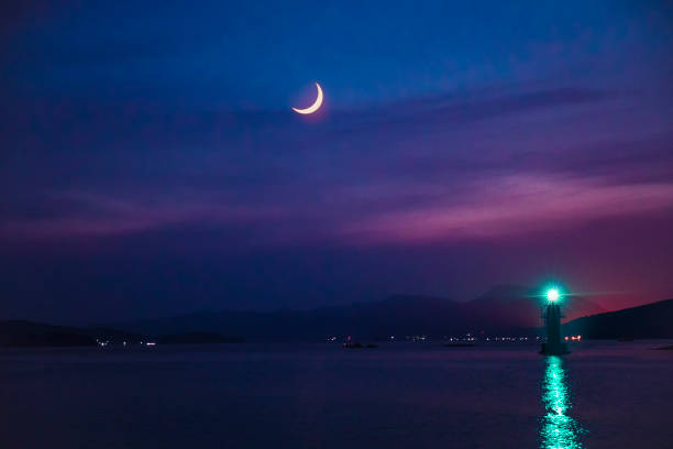 Lighthouse and crescent moon - summer night background stock photo