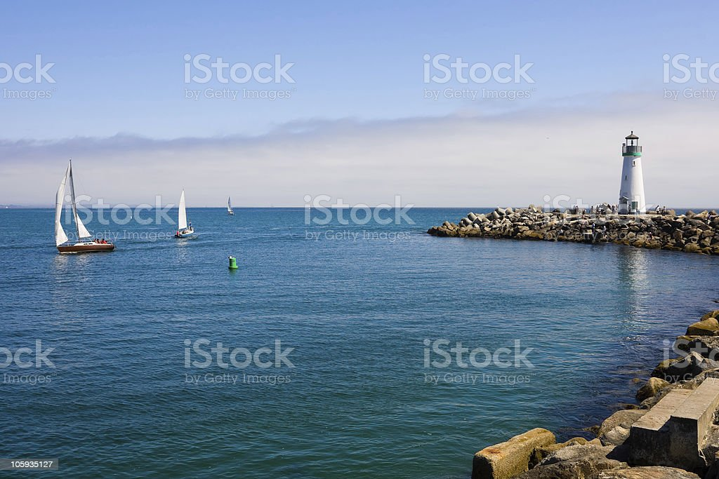Lighthouse and sail boats stock photo