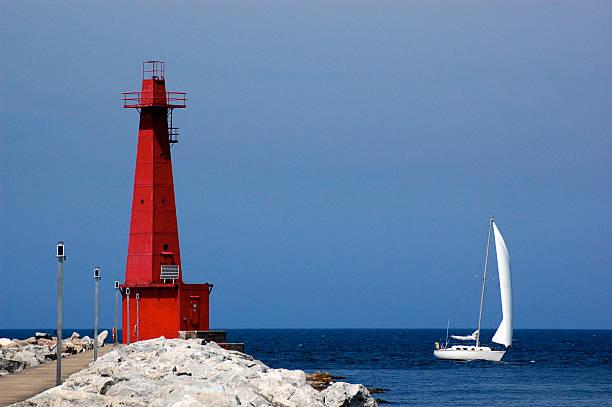 Lighthouse and sailboat, Muskegon, MI stock photo
