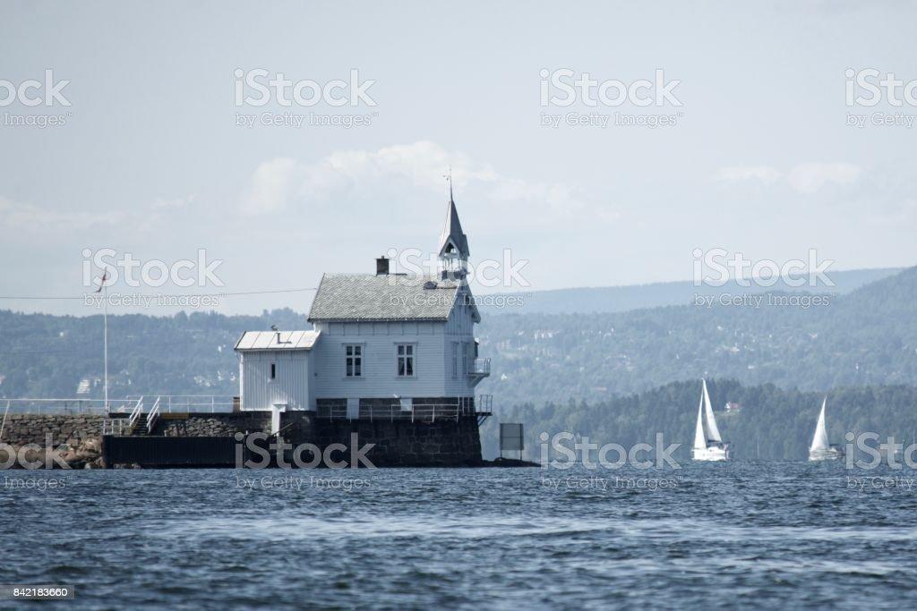 Lighthouse and sailboats stock photo