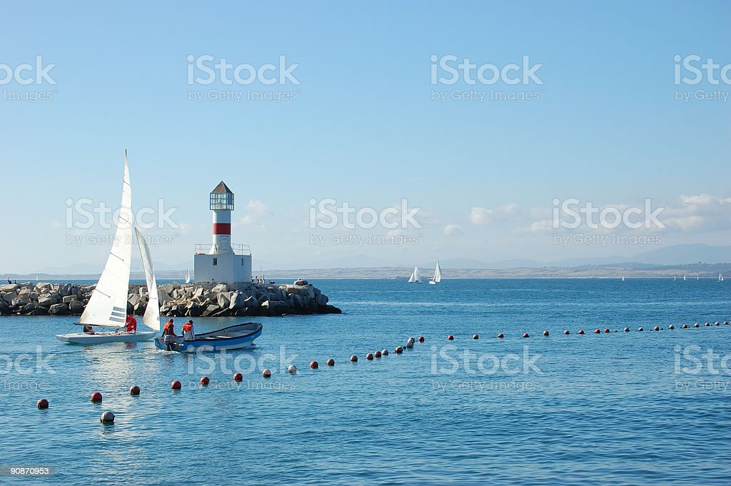Lighthouse and Sailing Boat stock photo
