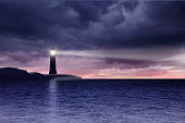 Lighthouse and seascape with dark clouds at night background
