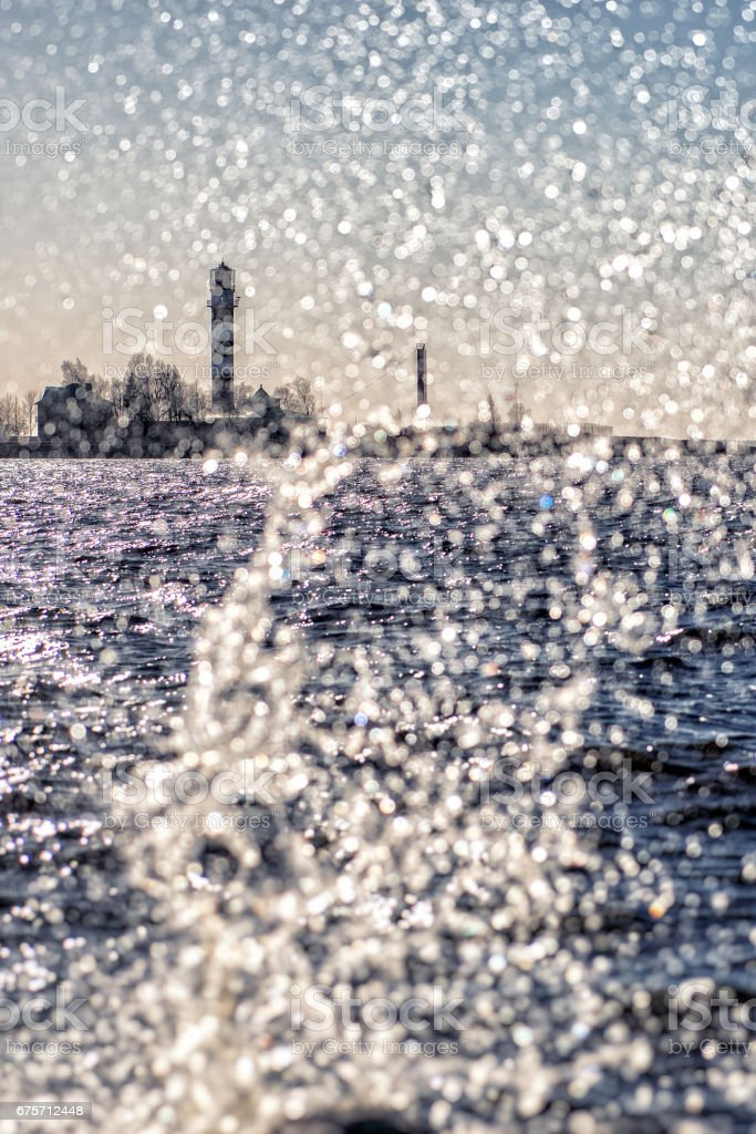 Lighthouse and wave splashes on a sunny day. royalty-free stock photo