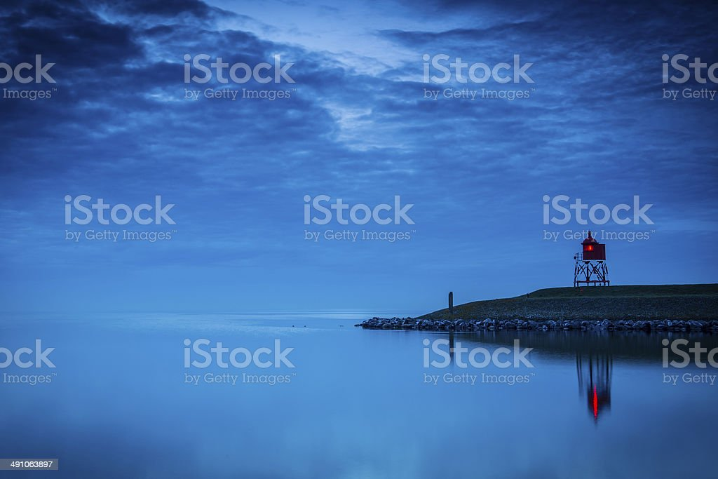 Lighthouse at a pier during twilight stock photo