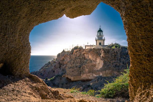 Lighthouse at Akrotiri through a frame of a window of a cave, Santorini, Greece. stock photo