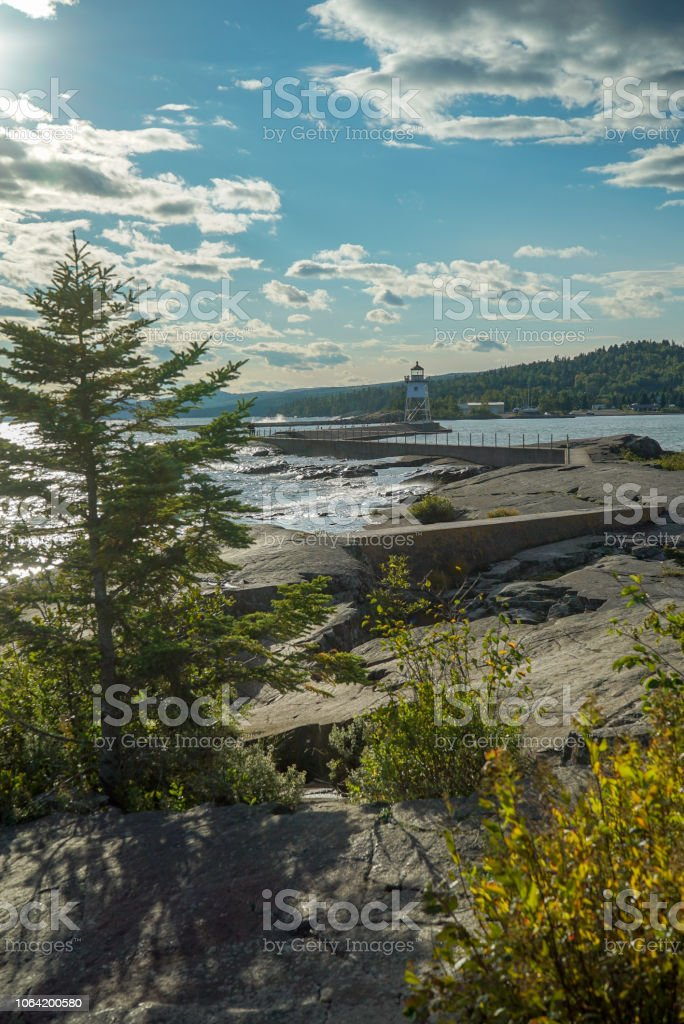 Lighthouse at Artists Point in Grand Marais Minnesota on a Sunny Day with Clouds stock photo
