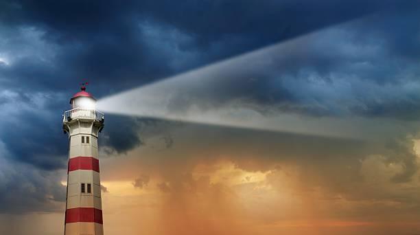 lighthouse à l'aube, le mauvais temps en arrière-plan - phare photos et images de collection