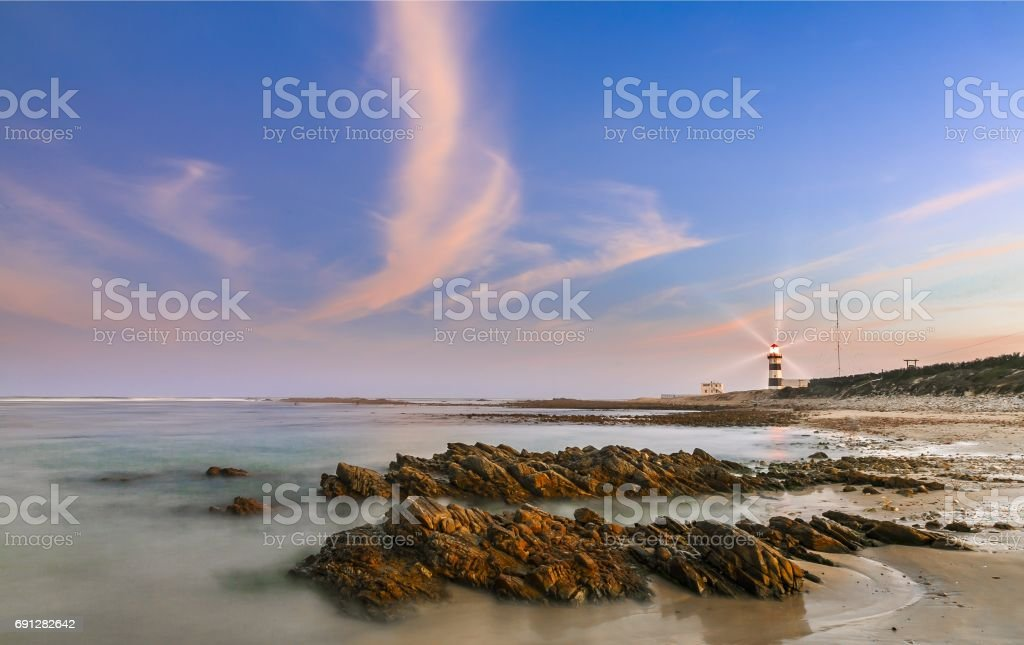 Lighthouse at dusk with rocks in the foreground stock photo