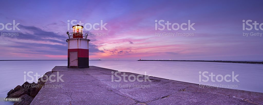 Lighthouse at harbour entrance in IJmuiden, The Netherlands at dusk stock photo