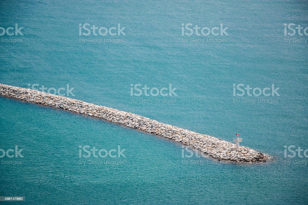 Lighthouse at horizon of breakwater. stock photo