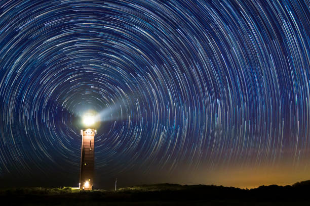 Lighthouse at night with star trails at the center Lighthouse at night with star trails at the center at Ouddorp, the Netherlands beacon stock pictures, royalty-free photos & images