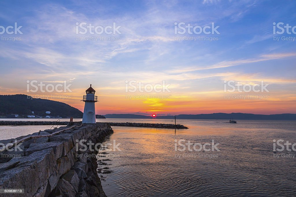 Lighthouse at sunset by the Fjord stock photo