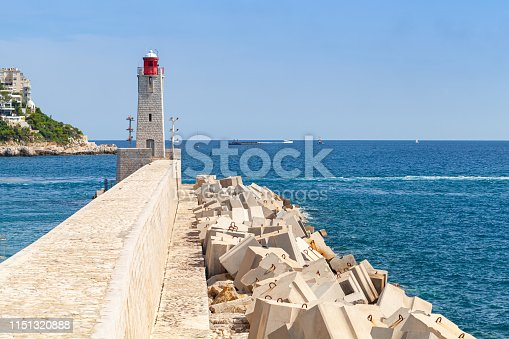 Lighthouse with red top stands on the end of concrete breakwater in French Riviera, Entrance to the Port of Nice, France