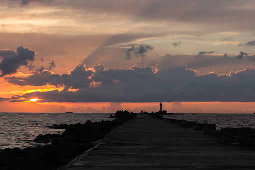 Lighthouse at the entrance to the port of Riga in the evening on sunset light, in summer