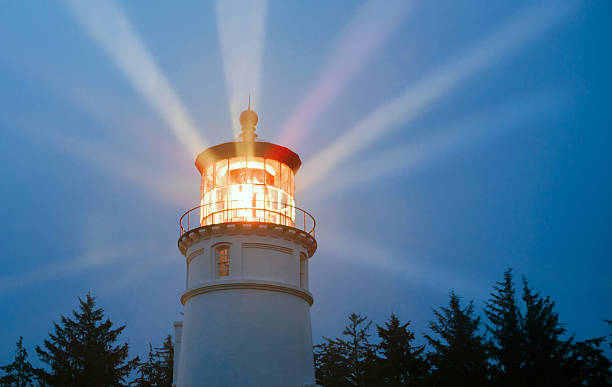 Lighthouse Beams Illumination Into Rain Storm Maritime Nautical Beacon stock photo