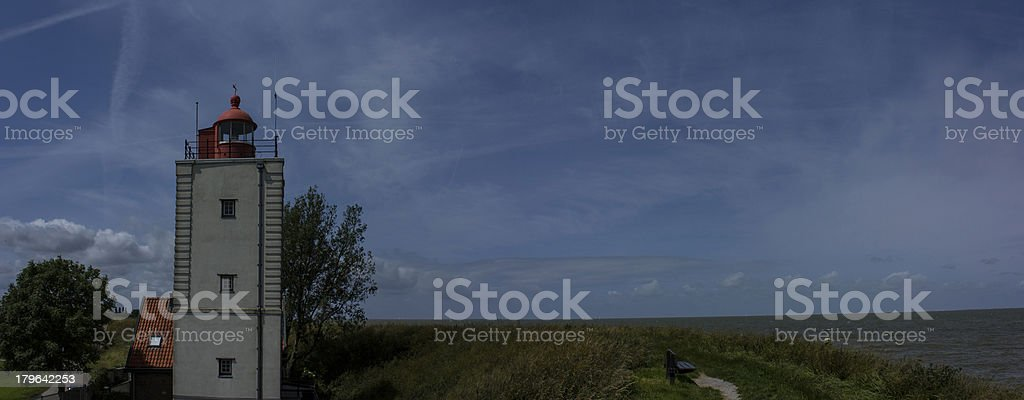 Lighthouse behind the dike royalty-free stock photo