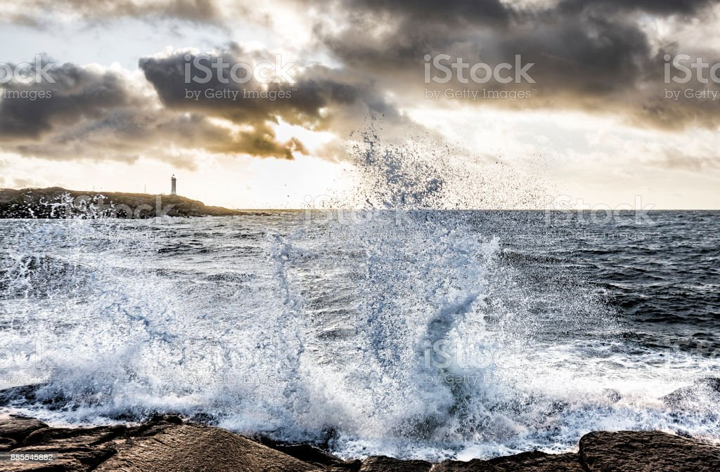 Lighthouse during stormy waters stock photo