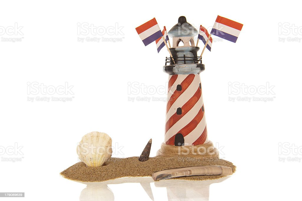Lighthouse Dutch flags sea shells sand royalty-free stock photo