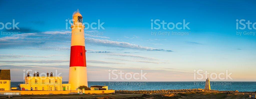Lighthouse illuminated by golden sunlight overlooking blue ocean horizon panorama stock photo