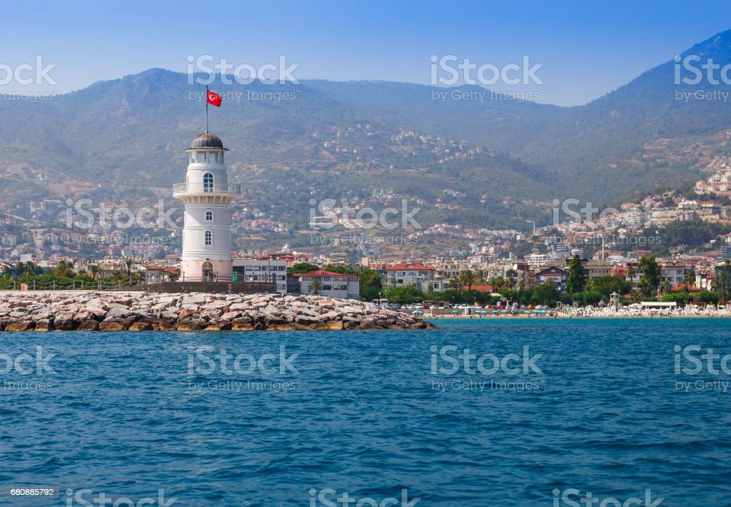 Lighthouse in Alanya, Antalya district, Turkey, Asia. View on city from boat. Popular tourist destination. Clear water in sunny day. royalty-free stock photo