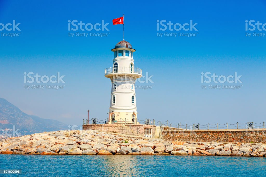 Lighthouse in Alanya, Antalya district, Turkey, Asia. View on city from boat. Popular tourist destination. Clear water in sunny day. stock photo