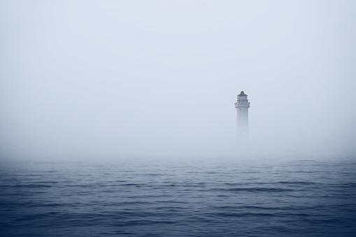 Lighthouse in foggy sea
