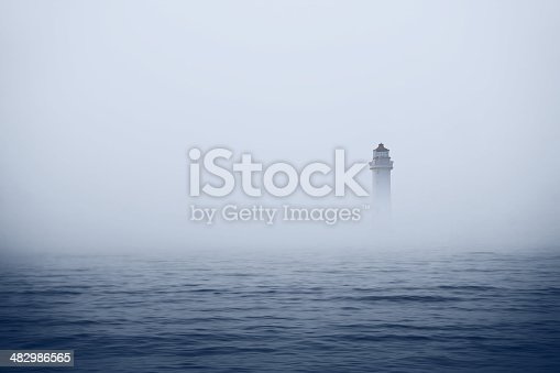 Lighthouse in foggy sea